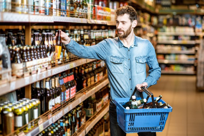 Man holding a shopping basket filled with beer bottles while lifting a beer bottle off a store shelf