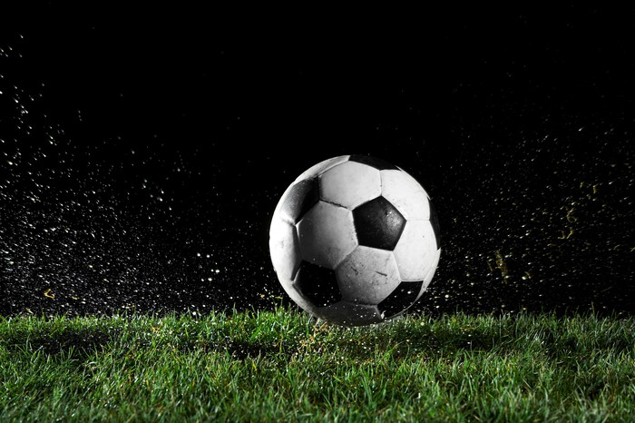 A soccer ball on wet grass at night.