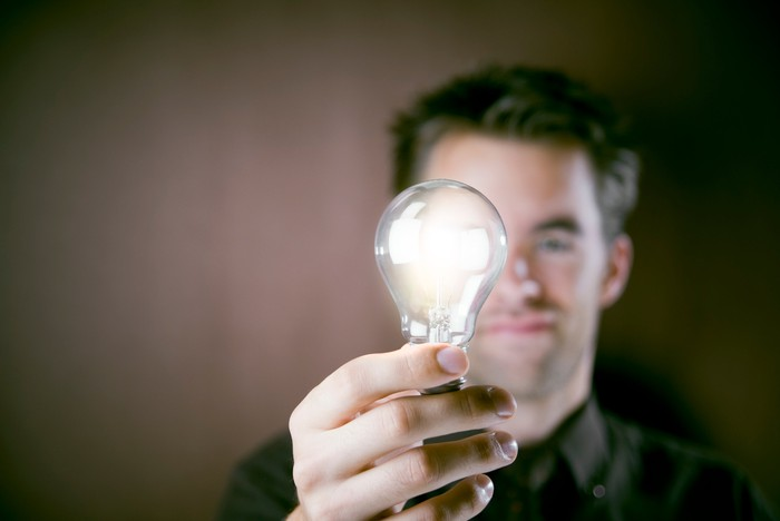 Man holding a lit lightbulb