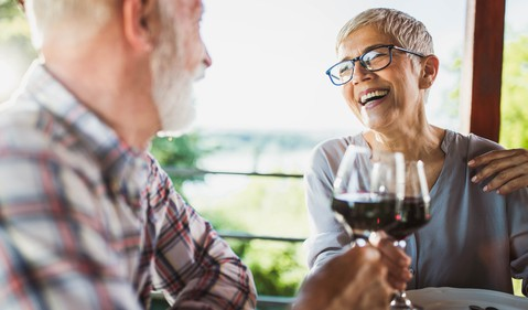 Smiling older man and woman clinking wine glasses_GettyImages-1192644574