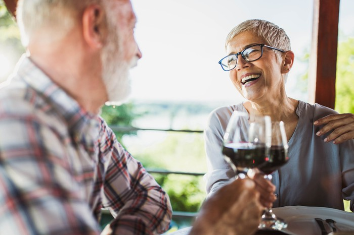 A smiling older man and woman clinking wine glasses.
