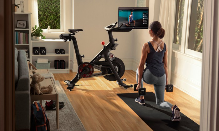 Woman kneeling with weights while watching a workout on a Peloton Bike+ screen