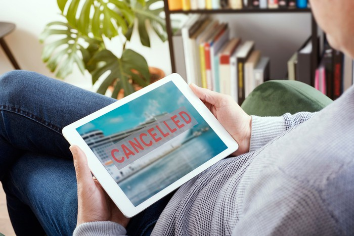 """A man looking at a tablet, which shows an image of a cruise ship with """"CANCELLED"""" superimposed over it in red lettering."""