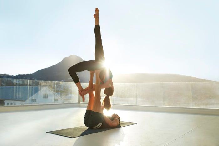 Un homme et une femme pratiquant le yoga.