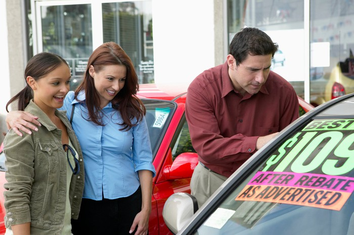 A man, woman, and young adult looking at a car on a used car lot.