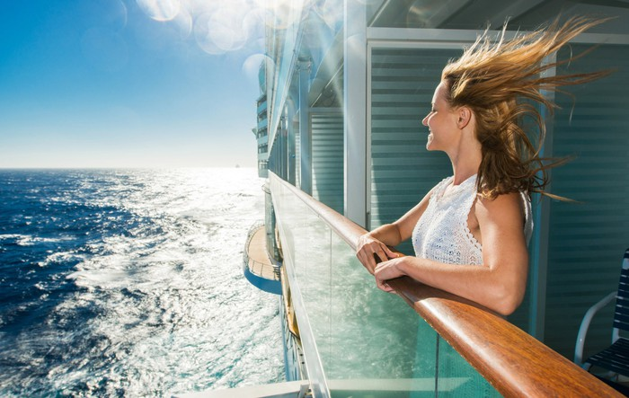 A smiling woman at a cruise ship rail looking out over a sunlit sea with her hair blowing in the wind.