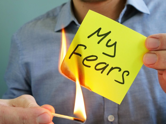 """Someone lighting on fire a sticky note that reads """"my fears"""""""