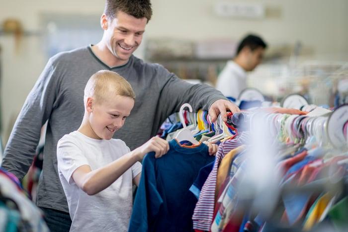 A man and child looking at shirts.