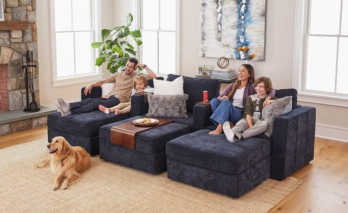 A man, woman, a girl, and a boy sitting on a dark blue modular sofa.