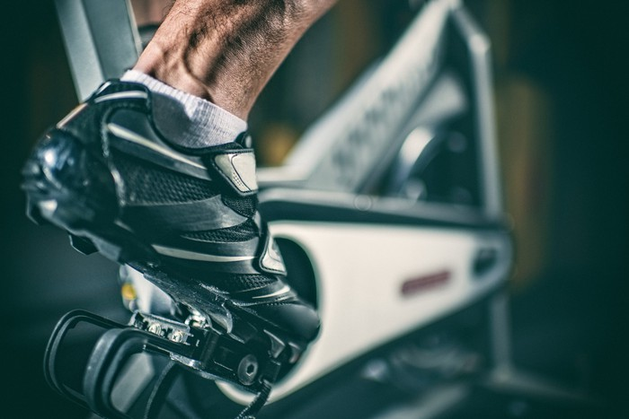 A foot on a pedal of an exercise bike.