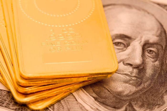 A messy stack of gold ingots laid atop a one hundred dollar bill next to Ben Franklin's image.