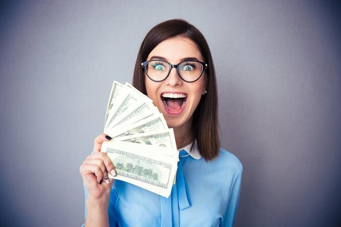 Femme tenant de l'argent et souriant.