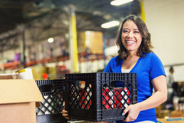 A woman holing a crate in a warehouse.