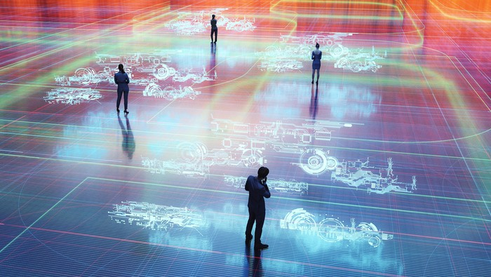 Four people standing in a space with the floor lit up with images of machinery