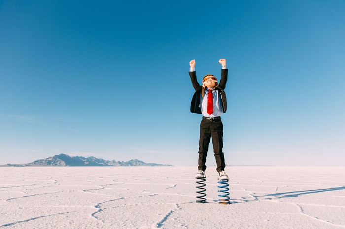 A young boy in a business suit stands on springs in the middle of a desert.
