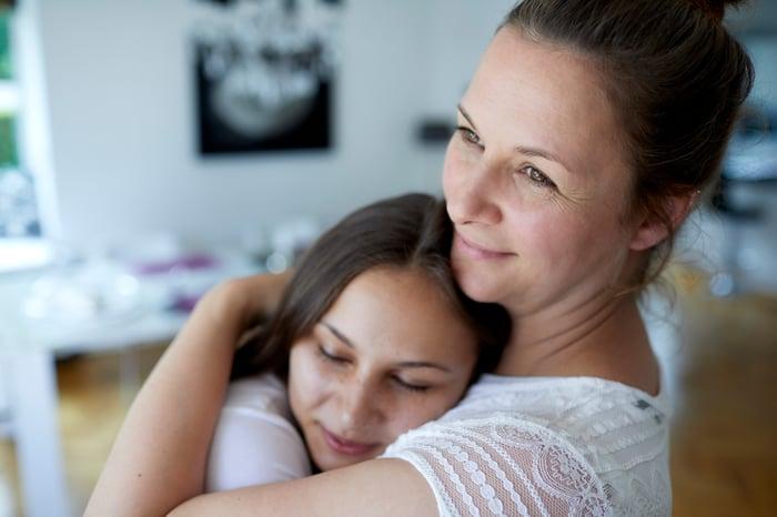 A mom hugs her teenage daughter in their living room.