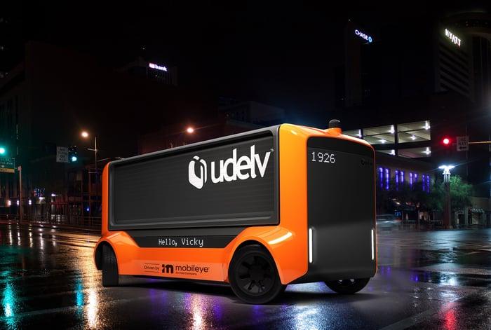 A Udelv Transporter, an orange and black self-driving van.