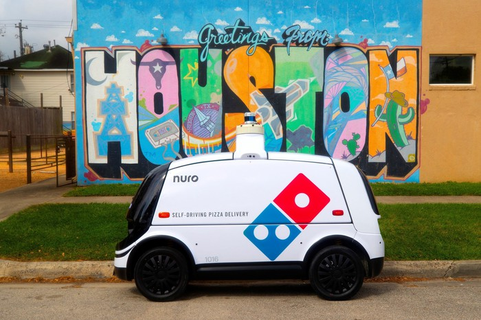 A Domiino's-branded Nuro R2 delivery robot parked at the curb in front of a colorful Houston sign.