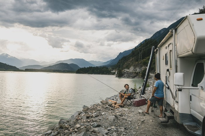 A family fishing with their RV parked on a lakeshore, with a cloudy, mountainous background.