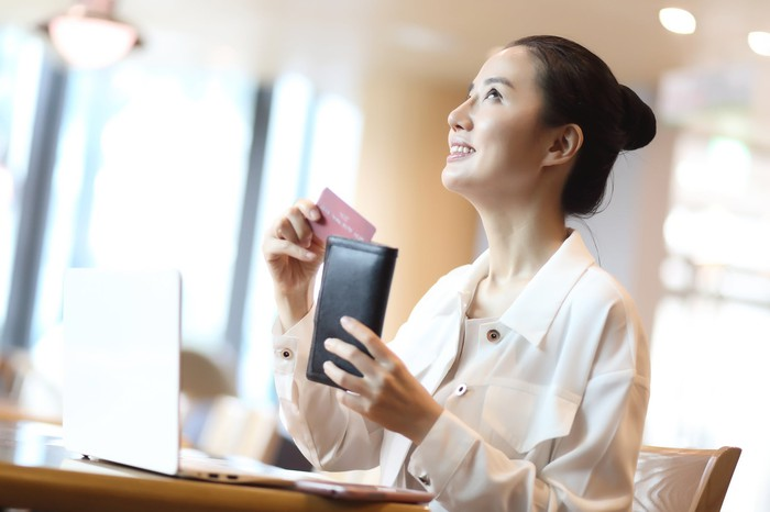 Woman in coffee shop taking out credit card to make purchase