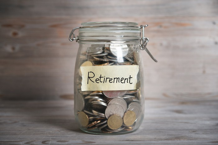 A mason jar full of coins labeled Retirement.
