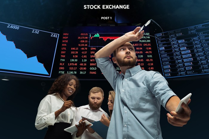 stock traders talking in front of a stock exchange board