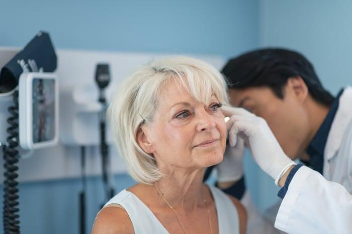 A doctor checks a woman's ear.