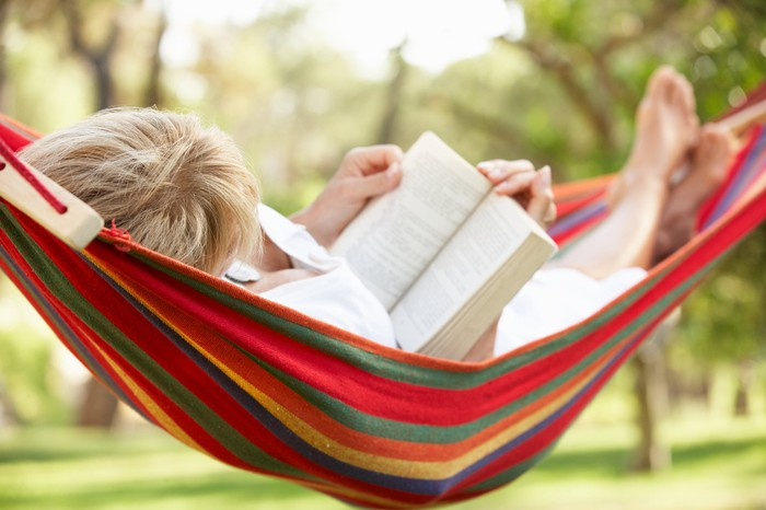 Woman resting, reading a book in a hammock.