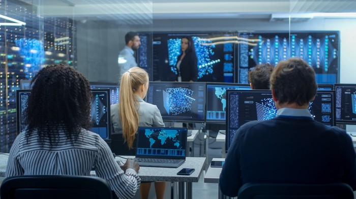 A team of computer technicians in a room with a bank of monitors working on artificial intelligence.