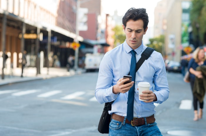 A man walking down the street looking at his phone