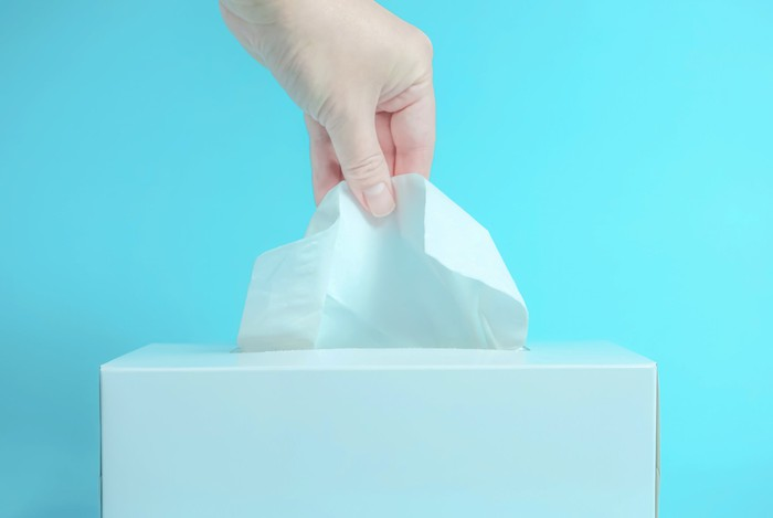 A person pulls a tissue out of a tissue box.