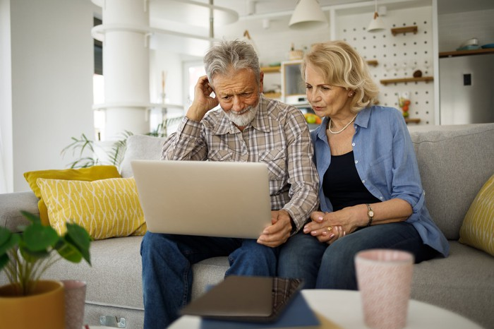 Older man and woman sitting on couch, looking at laptop