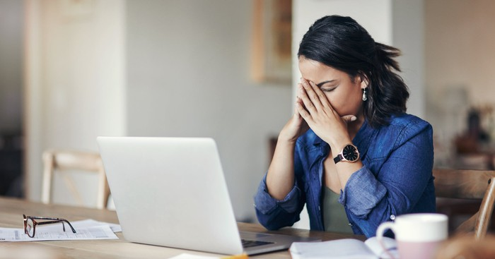 An investor expresses her frustration while sitting in front of a computer.