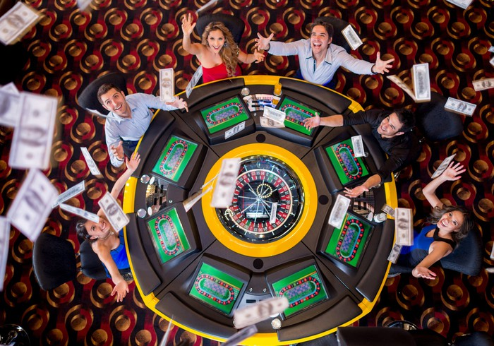 overhead view of casino players throwing cash in the air