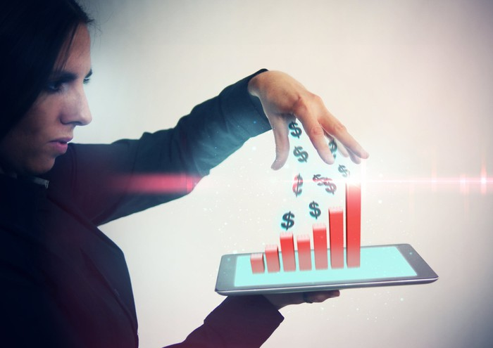 A woman holds a tablet that has a bar graph and dollar signs coming out of it.