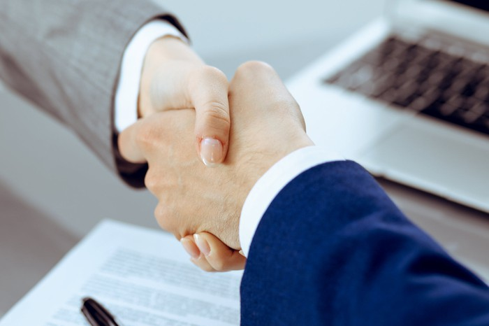 The hands of two executives shaking hands over a freshly signed contract.
