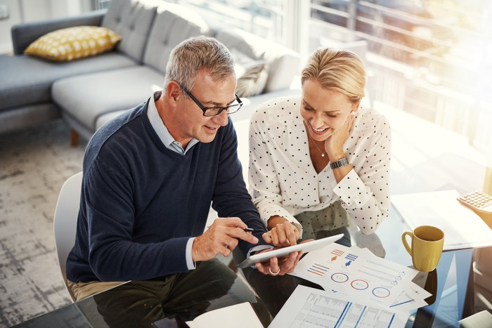 A middle-aged couple looking over finances on their tablet with charts and financial statements scattered on their desk.