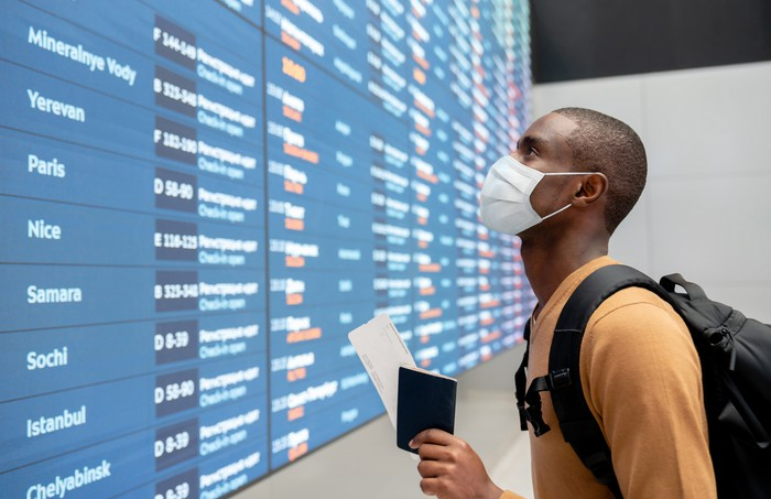 A man wearing a mask, holding his passport and airplane ticket, looking for his flight on the digital board at the airport