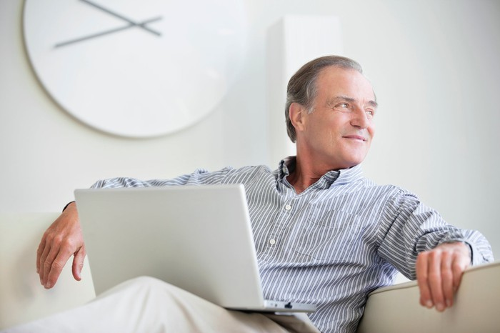 Mature man sitting with a laptop on his lap and smiling.