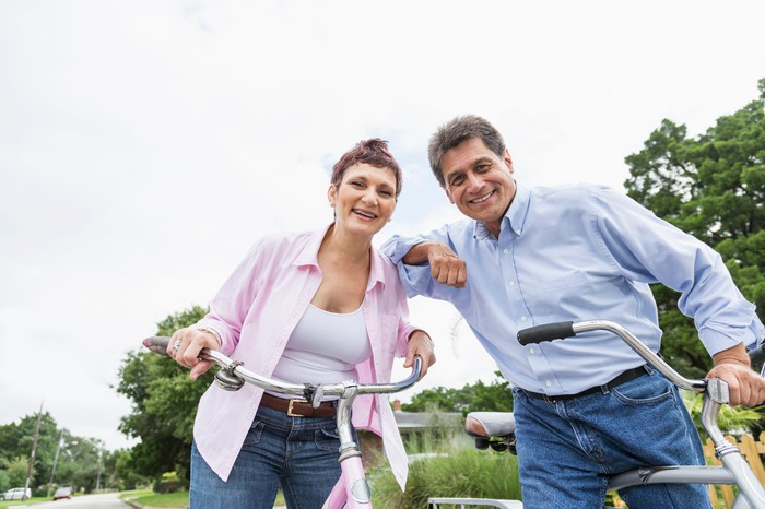 Mature man and woman smile while riding their bicycles outdoors.