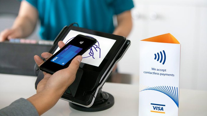 A person using stored credit card info on their smartphone to make a contactless payment.