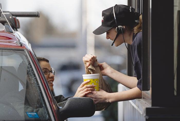 Fast food employee handing an order to a customer through a drive-thru window.