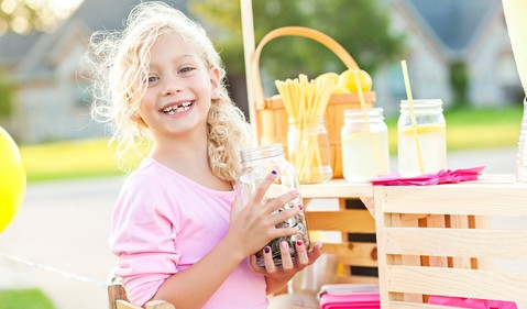 A girl with a lemonade stand holding a jar of coins