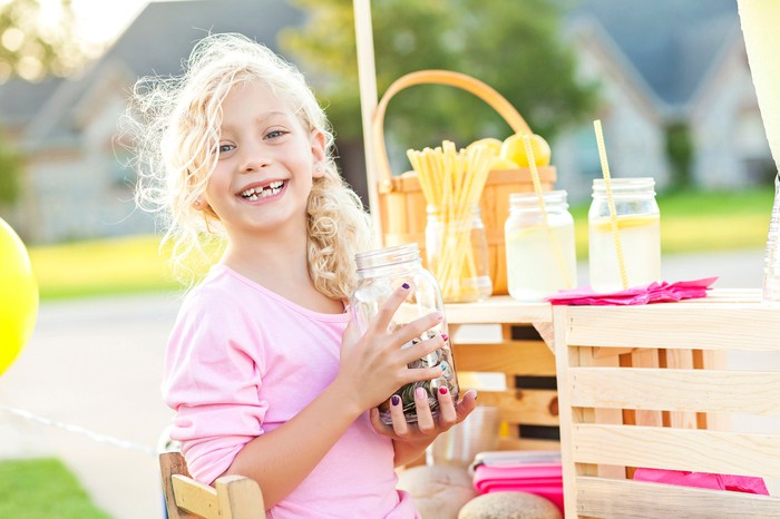 A girl with a lemonade stand holding a jar of coins.