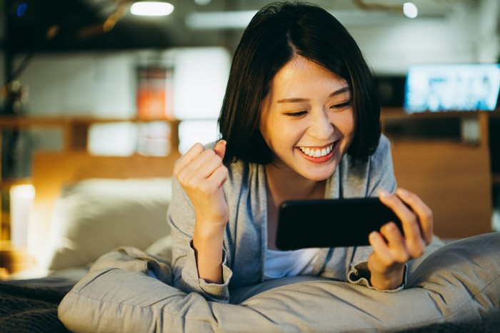 A young woman plays a mobile game while reclining on a bed.