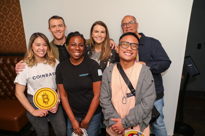 group of coinbase employees with one holding a bitcoin symbol