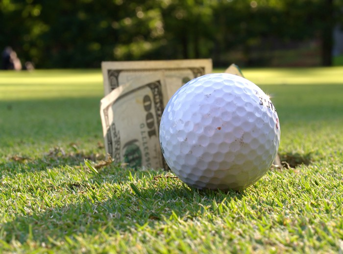 Ground-level view of golf ball on the green and $100 bills in the hole.