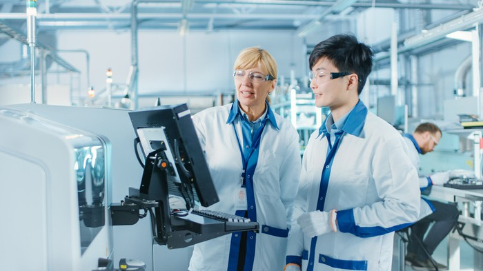 Two pharmaceutical manufacturing plant employees wearing gloves, goggles, and white jackets look at a computer screen together.