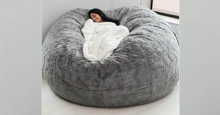 A woman resting with a blanket in a large Lovesac beanbag chair.