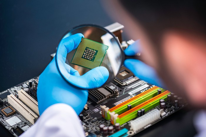 A hand holds a computer chip under a magnifying lens just above a circuit board in the background.